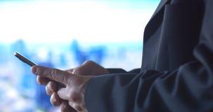 Geschäftsperson, die beweglichen Handytechnologie-Stadthintergrund verwendet