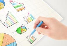 Geschäftsperson, die bunte Diagramme und Ikonen auf Papier zeichnet Stockfotografie