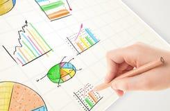 Geschäftsperson, die bunte Diagramme und Ikonen auf Papier zeichnet Stockbild