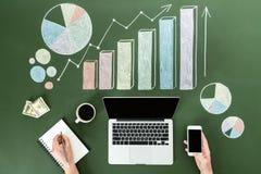 Geschäftsperson, die digitale Geräte am Arbeitsplatz mit bunten Diagrammen, Innenministeriumkonzept verwendet stockfotografie