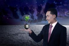 Geschäftsperson, die Glühlampe mit Anlage nach innen hält lizenzfreie stockbilder