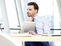 Geschäftsperson, die im Büro denkt Lizenzfreies Stockfoto