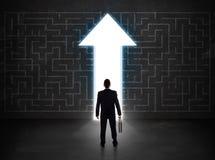 Geschäftsperson, die Labyrinth mit Lösungspfeil auf der Wand betrachtet Lizenzfreie Stockfotos