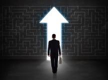 Geschäftsperson, die Labyrinth mit Lösungspfeil auf der Wand betrachtet Lizenzfreies Stockfoto
