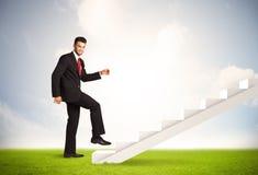 Geschäftsperson, die oben auf weißem Treppenhaus in der Natur klettert Lizenzfreie Stockbilder