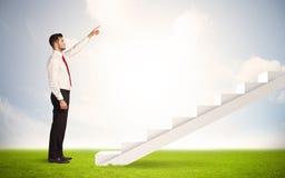 Geschäftsperson, die oben auf weißem Treppenhaus in der Natur klettert Lizenzfreie Stockfotos