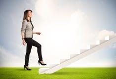 Geschäftsperson, die oben auf weißem Treppenhaus in der Natur klettert Stockfotos