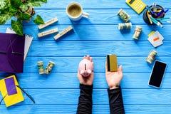 Geschäftsperson, die Sparschwein und Kreditkarte auf blauem Holztisch hält Stockfotografie