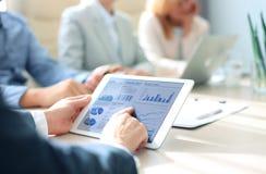 Geschäftsperson, welche die Finanzstatistik angezeigt auf dem Tablettenschirm analysiert Lizenzfreie Stockfotos