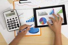 Geschäftsperson, welche die Finanzstatistik angezeigt auf dem Tablettenschirm mit einem Stift analysiert lizenzfreies stockfoto