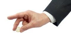 Geschäftspersonenhand, die eine Euromünze getrennt auf Weiß anhält Lizenzfreie Stockfotografie