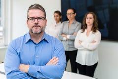 Geschäftsporträt des Mannes mit drei Frauen im Hintergrund Lizenzfreie Stockfotos