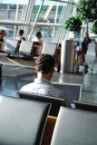 Geschäftsreisender, der in einen Flughafenaufenthaltsraum wartet stockfoto