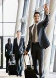 Geschäftsreisender, der Koffer und das Gestikulieren zieht Stockfoto
