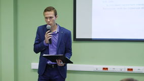 Geschäftsschüler spricht auf ein Seminar für Finanzierung Junger Mann benutzt ein Mikrofon und einen Projektor für seine Rede stock footage