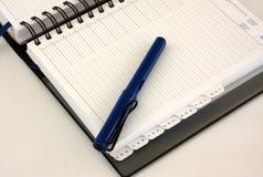 Geschäftstagebuchorganisator mit blauer Feder Lizenzfreie Stockbilder