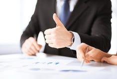 Geschäftsteam auf Sitzung Grafiken besprechend Lizenzfreie Stockfotografie