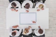 Geschäftsteam, das auf leeres Papier zeigt stockfotografie