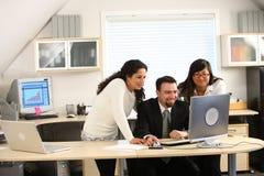 Geschäftsteam, das Computer betrachtet Stockbilder