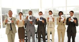 Geschäftsteam, das die Buchstaben bedeuten Erfolg hält stock video