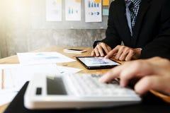 Geschäftsteam, das Dokumente Taschenrechneranalyse-Daten auf digitaler Tablette verwendet lizenzfreies stockbild