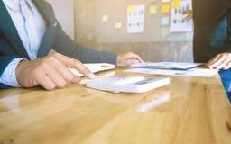 Geschäftsteam, das Dokumente Taschenrechneranalyse-Daten verwendet und Taschenrechner mit stockbilder