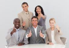 Geschäftsteam, das einen Erfolg mit den Daumen oben feiert Lizenzfreie Stockfotos
