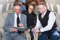 Geschäftsteam, das in Geschäftsflugzeug reist und ein presen bespricht Lizenzfreies Stockfoto