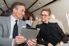 Geschäftsteam, das in Geschäftsflugzeug reist und ein presen bespricht Stockbilder