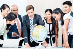 Geschäftsteam, das globale umfassende Marktinformation bespricht Stockbild