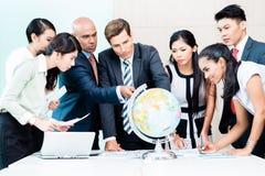 Geschäftsteam, das globale umfassende Marktinformation bespricht Lizenzfreies Stockbild