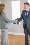 Geschäftsteam, das Hände und das Lächeln rüttelt Lizenzfreie Stockfotografie