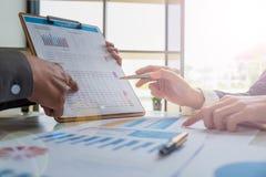 Geschäftsteam, das Haushaltsplan und Statistik analysiert stockbild