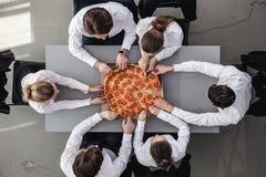 Geschäftsteam, das Pizza isst stockfoto