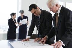Geschäftsteam, das Pläne während der Sitzung wiederholt. Stockbild