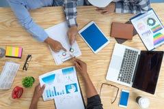 Geschäftsteam, das um Tabelle sitzt und mit Papierdiagrammbericht arbeitet erfolgreiche Partner, die Unternehmensplan am Treffen  lizenzfreie stockbilder
