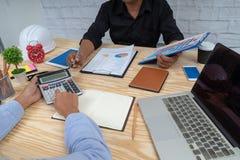 Geschäftsteam, das um Tabelle sitzt und mit Papierdiagrammbericht arbeitet erfolgreiche Partner, die Unternehmensplan am Treffen  lizenzfreie stockfotografie