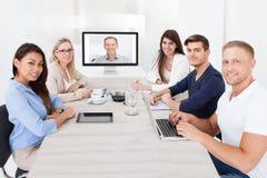 Geschäftsteam, das an Videokonferenz teilnimmt Stockbild