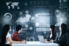 Geschäftsteam, das virtuelle Finanzdiagramme bespricht Stockfotografie