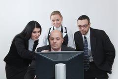 Geschäftsteam, das vor Überwachungsgerät behandelt Stockbild