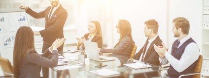 Geschäftsteam, das zum Manager Finance auf der Darstellung des neuen Projektes an dem Arbeitsplatz applaudiert stockfoto
