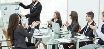 Geschäftsteam, das zum Manager Finance auf der Darstellung des neuen Projektes an dem Arbeitsplatz applaudiert lizenzfreies stockbild
