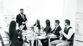 Geschäftsteam, das zum Manager Finance auf der Darstellung des neuen Projektes an dem Arbeitsplatz applaudiert lizenzfreie stockfotografie