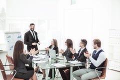Geschäftsteam, das zum Manager Finance auf der Darstellung des neuen Projektes an dem Arbeitsplatz applaudiert stockbild