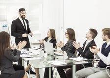 Geschäftsteam, das zum Manager Finance auf der Darstellung des neuen Projektes an dem Arbeitsplatz applaudiert stockbilder