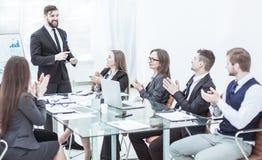 Geschäftsteam, das zum Manager Finance auf der Darstellung des neuen Projektes an dem Arbeitsplatz applaudiert lizenzfreies stockfoto
