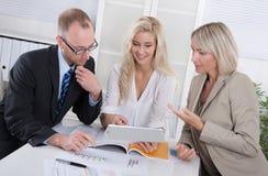 Geschäftsteam des Mannes und der Frau, die um Schreibtisch in einer Sitzung sitzen stockfoto