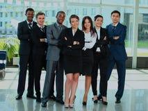 Geschäftsteam in einer Zeile lächelnd an der Kamera Lizenzfreie Stockfotografie