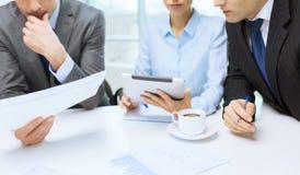 Geschäftsteam mit Diagramm, Tabletten-PC und Kaffee Stockfotos