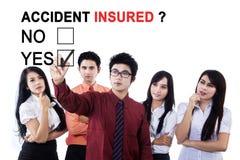 Geschäftsteam mit Frage von Unfallversicherten Stockfotografie